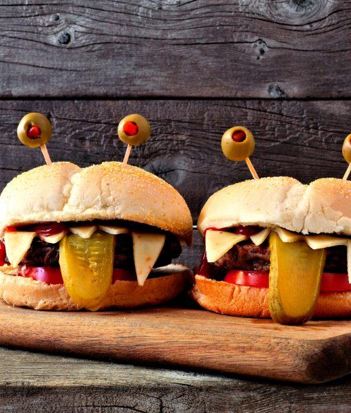 Halloween monster hamburgers against old wood